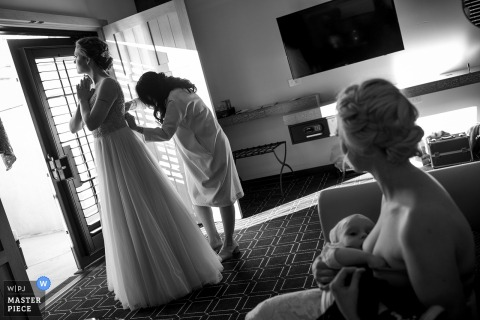 Bridesmaid watches as the bride finishes getting her dress ready for the wedding at Hotel Valencia in San Jose, California
