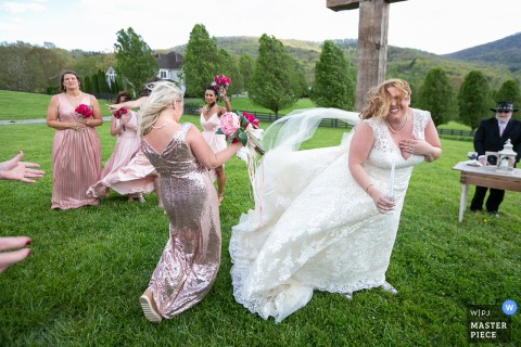 Bridesmaid and the bride trying to manage her dress outside in the wind at the Aska Farms, Blue Ridge