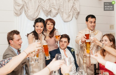 Historic Rosemont Manor photography - the bride and groom are surrounded by guests as they all toast their drinks