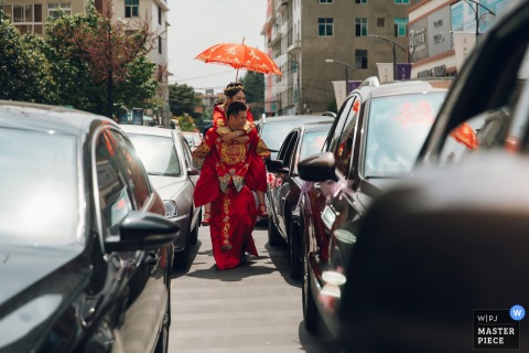 China groom carries the bride with an umbrella through the cars stopped on the road