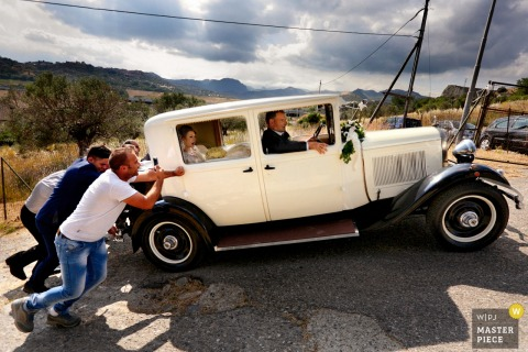 Calabria men pushing the bride and grooms car after the wedding