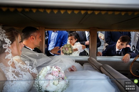 Reggio Calabria bride inside the limousine with children looking in - wedding photographer