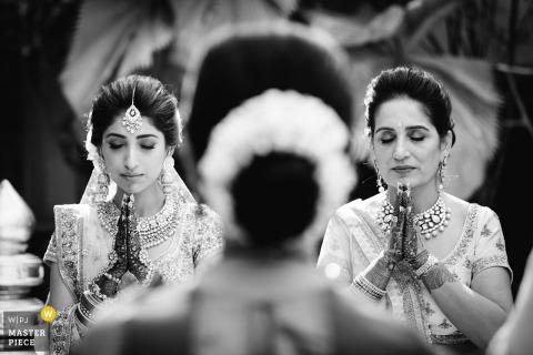 Mumbai, India bridesmaid and maid of honor pray at the wedding ceremony