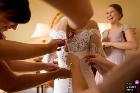 Castlemartyr, Cork bride getting help with her dress with her bridesmaids before the wedding