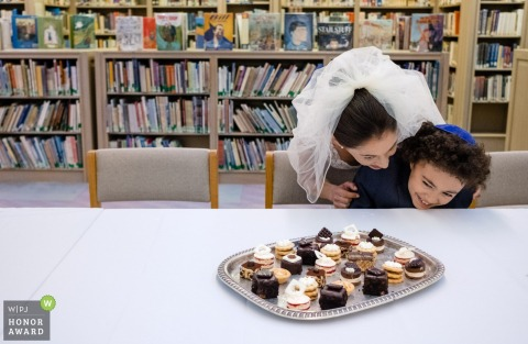 Adas Israel Congregation Washington DC wedding photographer - the bride laughs with the child before a tray of sweets at the library