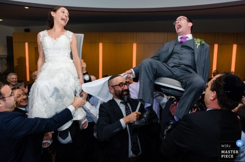 Bride and groom laugh as they get carried on chairs by the guests at the Adas Israel Congregation, Washington DC