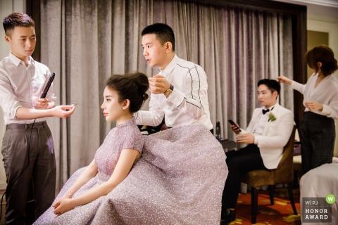 Yangzhou, Jiangsu, China bride and groom receive help with their hair