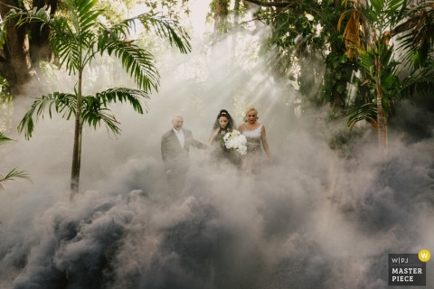 Miami, Florida bride walks with her mother and father in the fog and trees