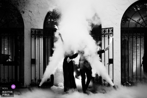 Miami, Florida bride and groom hold hands and wave through the smoke at the wedding reception