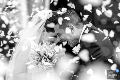 Lombardy bride and groom smiles and laugh as flowers fall around them at the wedding