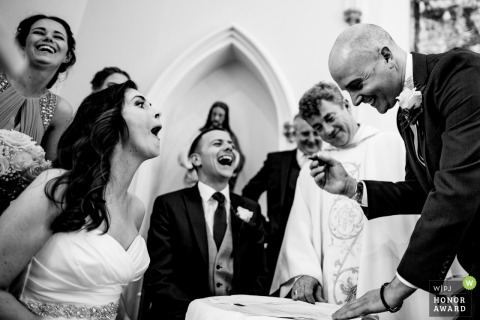 Louth, Ireland Church wedding photographer - the bride and groom laugh with guests during the signing of the official marriage certificate