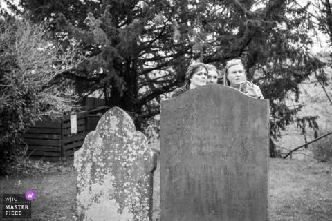 Claverley, Shropshire bride and bridesmaids stand behind a tombstone at the wedding