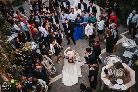 Sardinia bride does the limbo at her courtyard wedding reception - overhead wedding photo shots