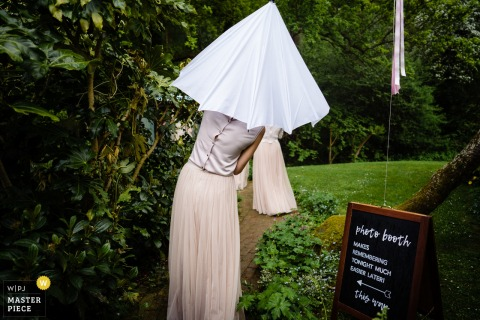 Bridesmaid trying to avoid the rain with an umbrella at the wedding at Bartolomew Barns, East Sussex