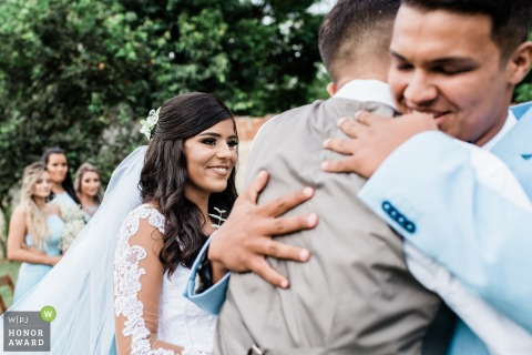 Rio de Janeiro groom hugs a friend with his bride at his side - wedding photographer for outdoor ceremonies