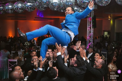 Groomsmen throw the groom into the air at the wedding reception in Espaco Reviver Sete, Lagoas