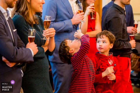 Netherlands boy finishes a drink as the boy next to him watches at the wedding reception