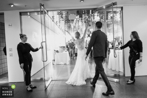 Laguna Beach, California wedding photographer - wedding vendors hold the glass doors wide open for the bride and groom as they enter their reception