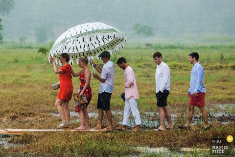 Guestings holding umbrella for the ladies as it rains at Paddy Island, Unawatuna, Sri Lanka