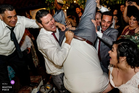 Sonoma, California guests flip the groom upside down at the wedding reception