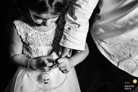 Valinhos girl holds the grooms finger at the wedding