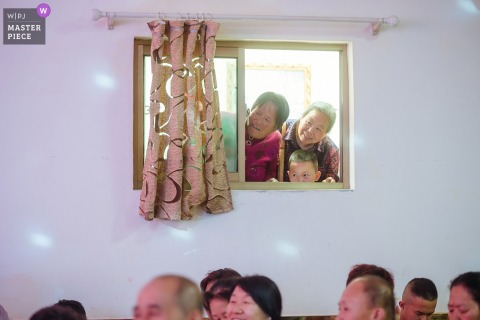 Shanxi, China guests looking though a window to see the wedding ceremony
