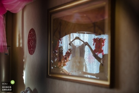 shanxi china wedding photography of the bride and her hanging dress reflected in a picture on the wall