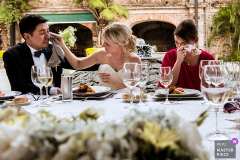 Mexico City bride wipes a tear off of the grooms face at the wedding reception