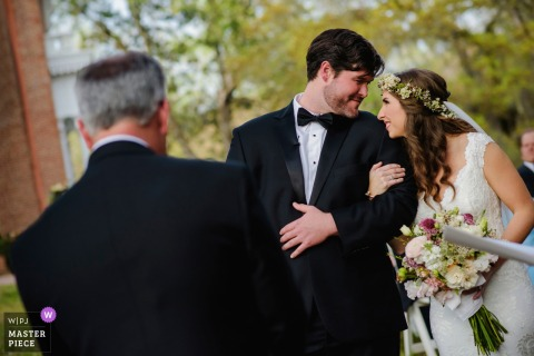 Natchez bride and groom smile at each other during the wedding ceremony