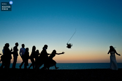Thorpeness, UK guests reach for the bouquet after the bride threw it at the sunset beach reception