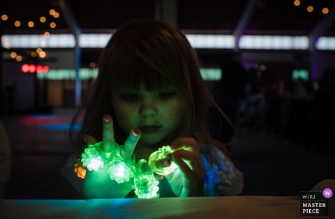 Omaha, Nebraska girl plays with light up toys at the wedding reception