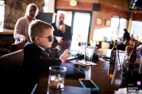 Young boy wears sunglasses at the table playing on the phone at the Cheyenne Mountain Resort, Colorado