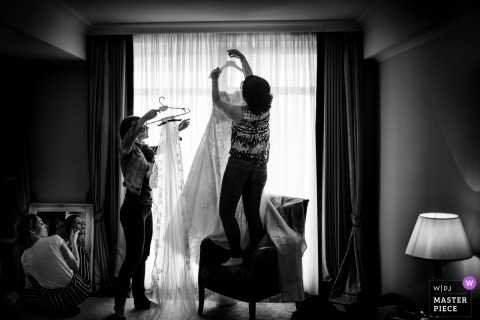 Kempinski women hanging up the brides wedding dress before the wedding ceremony