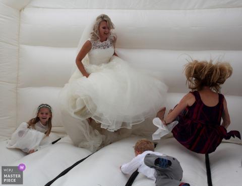 Newton Abbot, Devon bride plays with kids in a jump house