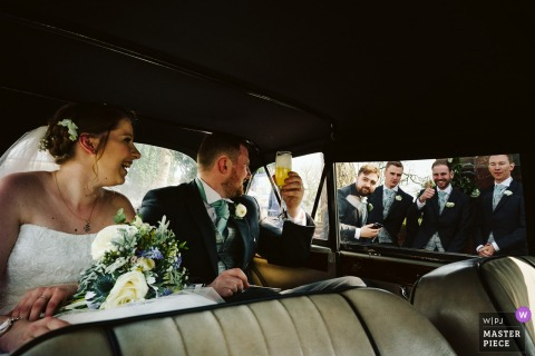 Cheshire, England bride and groom laugh with the groomsmen in the car after the wedding ceremony