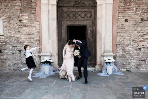Italia novia y el novio salen por la puerta después de la ceremonia