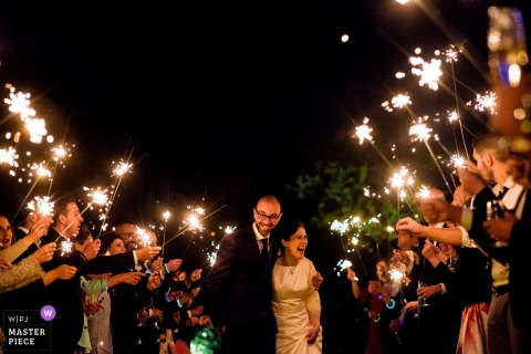 Braga, Portugal guests light sparklers in front of the bride and groom at the reception