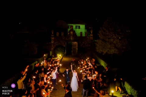 Braga, Portugal guests hold candles while the bride and groom walk down the aisle