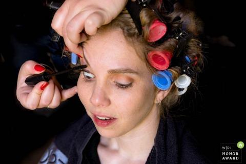 De bruid van Nederland heeft mascara aangebracht op haar wimpers terwijl ze zich nog in krulspelden bevindt - bruidsfotografie voor bruidsvoorbereiding