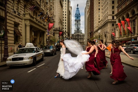 New Jersey bridesmaids walking across the street holding the brides dress
