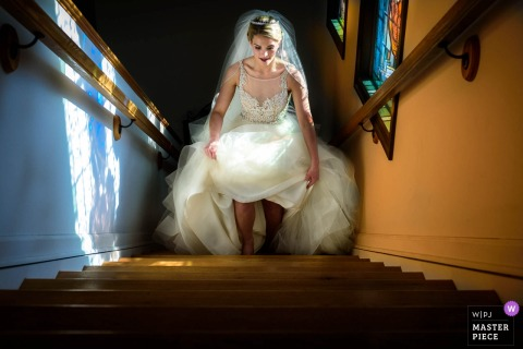 De bruid van New Jersey loopt de trap op terwijl ze haar jurk op de bruiloft vasthoudt