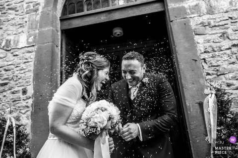 Lombardy bride and groom laugh as rice is thrown at them after the wedding ceremony