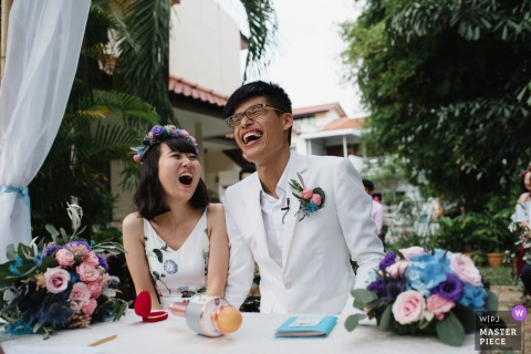 Singapore bride and groom laugh at the wedding reception
