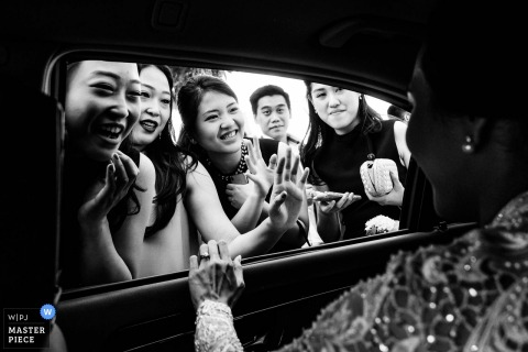 Bali bruid zwaait naar gasten uit in de auto na de bruiloft in het Ayana Resort