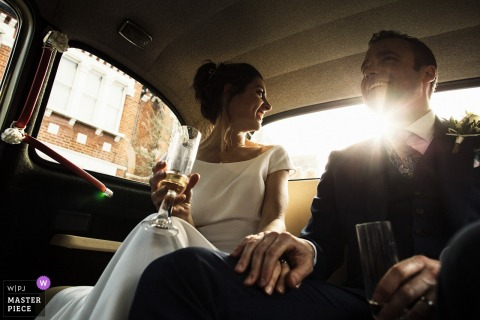 London, UK bride and groom hold hands and enjoy drinks while in the car after the wedding
