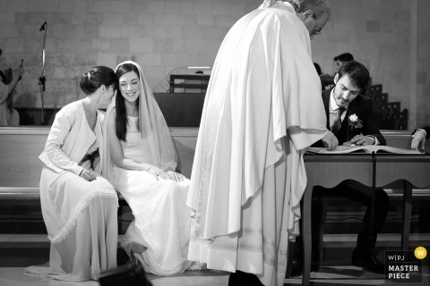 Apulia bride talks and smiles with maid of honor during the marriage certificate signing