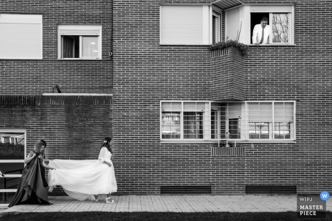 Alcalá de Henares, Madrid bride walking with bridesmaid holding the wedding dress