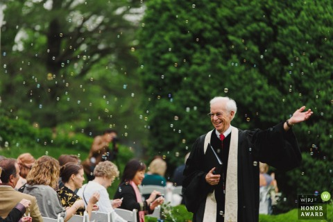 Leesburg, VA wedding photographer - this ceremony officiant enjoys the guests bubbles outside