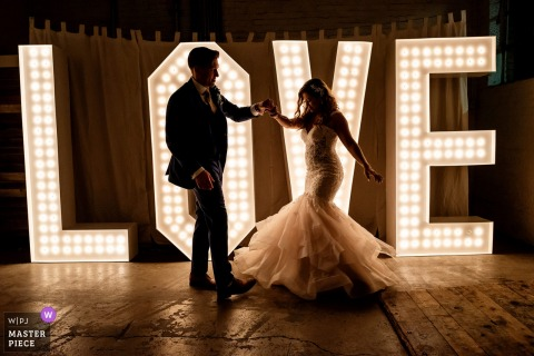 San Diego bride and groom stand in front of a sign that says love