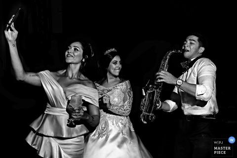 Die Brautjungfer von Goiania nimmt ein Selfie mit dem Saxophonisten auf der Hochzeitsfeier